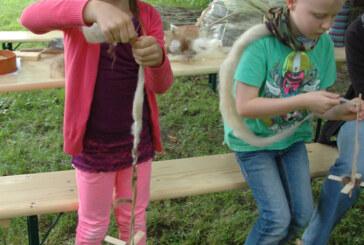 Kinder der Naturschutzjugend bauen Handspindeln und stellen Wolle her