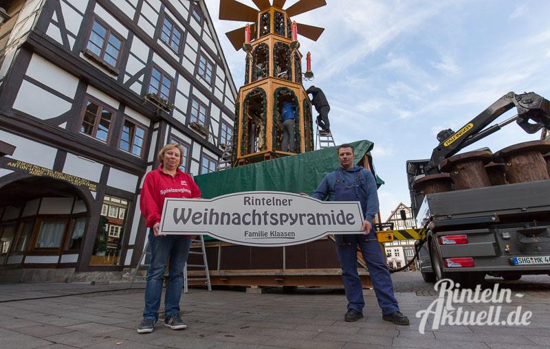 Silvia Bräuer von der Spielzeuginsel und Schausteller Marlon Klaasen präsentieren das neue Weihnachtspyramidenschild.