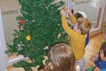 Kindergartenkinder schmücken Weihnachtsbaum